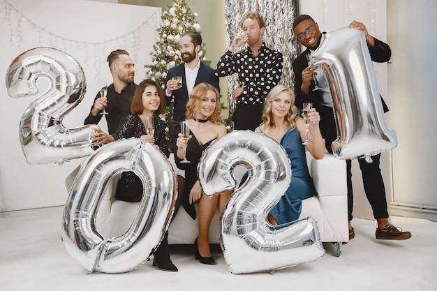 Pessoas em uma decoração christman. homem de terno preto. celebrações do grupo de ano novo. pessoas com balões 2021.