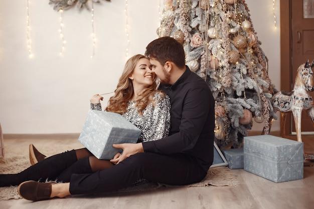 Pessoas em uma decoração de natal. homem com um suéter cinza. família em casa.