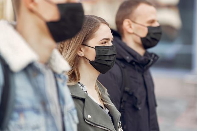 Pessoas em uma máscara fica na rua