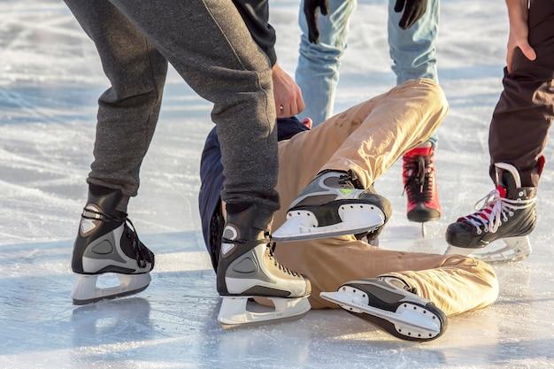 Pessoas em uma pista de gelo ajudam uma pessoa caída a se levantar. lesões e esportes na pista de gelo.