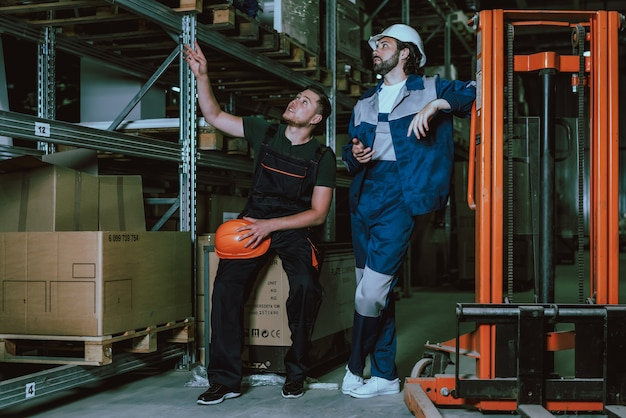 Pessoas em uniforme e capacete de segurança no intervalo no trabalho