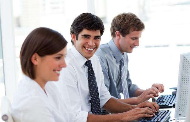 Pessoas empresariais positivas que trabalham em computadores