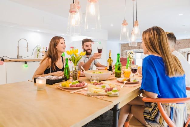 Pessoas encantadas bebendo durante o jantar