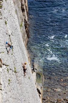 Pessoas escalando juntas em uma montanha abrupta