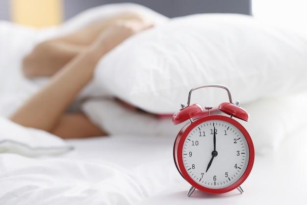Pessoas está cobrindo sua cabeça com um travesseiro ao lado de um despertador. conceito de acordar de manhã cedo