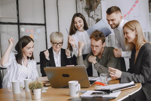 Pessoas estão trabalhando no projeto. homens e mulheres de terno sentados à mesa. os empresários usam um laptop.