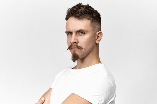 Pessoas, estilo, beleza masculina e conceito de moda. feche a imagem de um cara bonito hippie com olhar penetrante, bigode estiloso e cavanhaque, posando no estúdio, orgulhoso de si mesmo
