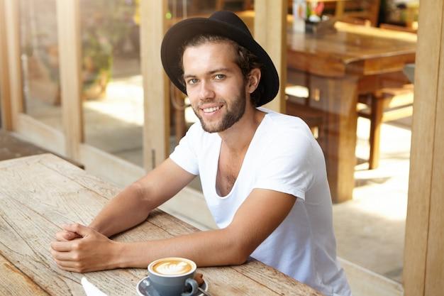 Pessoas, estilo de vida e lazer. retrato interior de bonito jovem hippie elegante chapéu preto, sentado à mesa de café de madeira com caneca de cappuccino