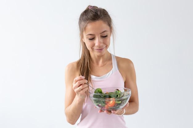 Pessoas, estilo de vida saudável e conceito de aptidão - mulher jovem e bonita após o treino, comendo salada saudável.