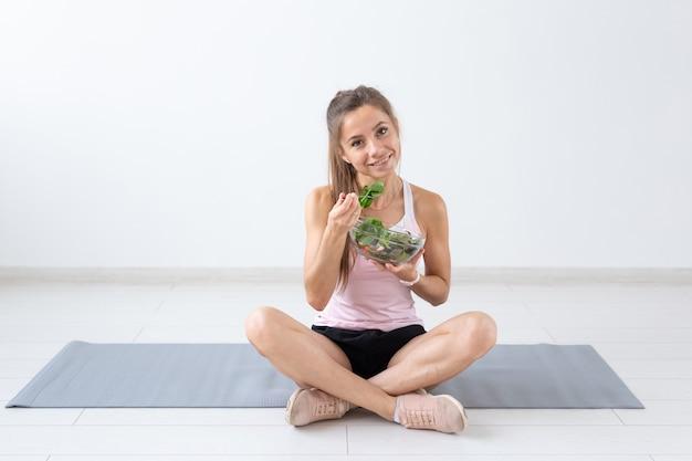 Pessoas, estilo de vida saudável e conceito de fitness - linda mulher sentada no chão após o treino e comendo salada saudável.