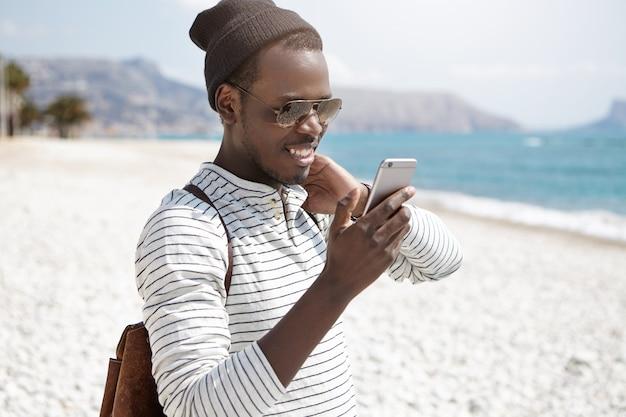 Pessoas, estilo de vida, viagens, aventura e conceito de tecnologia moderna. mochileiro americano africano alegre bonito no chapéu e óculos de sol, segurando o telefone móvel