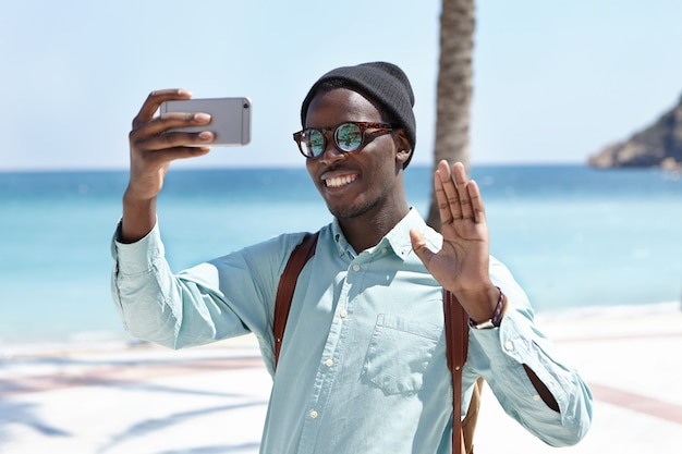 Pessoas, estilo de vida, viagens, turismo e tecnologia moderna. atraente viajante preto em elegantes tons e chapelaria posando para selfie com sorriso feliz e olá gesto contra o mar azul