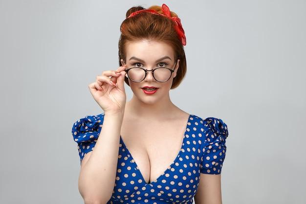 Pessoas, estilo, moda, ótica e óculos. foto isolada da linda modelo pin up girl em vestido decotado anunciando óculos no estúdio, segurando óculos elegantes e sorrindo para a câmera