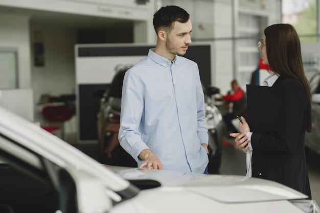 Pessoas estilosas e elegantes em um salão de automóveis