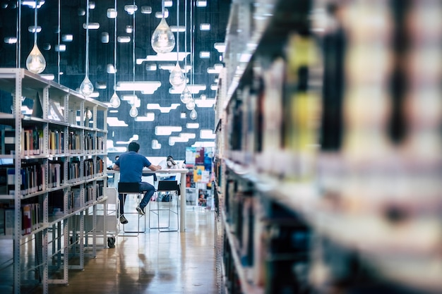 Pessoas estudando em uma biblioteca pública moderna - homem sentado, visto de costas, trabalhando em um computador laptop - espaço da cidade para os alunos aprenderem e ensinarem