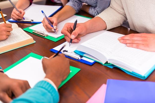 Pessoas, estudantes sentados em uma mesa na sala de aula.