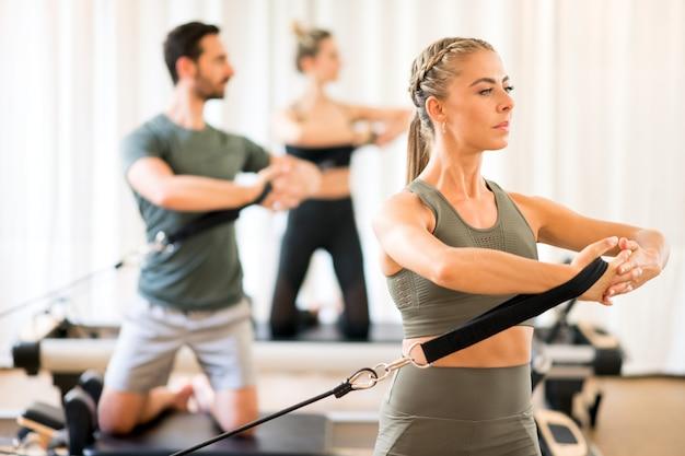Pessoas exercitando rotação do tronco no ginásio