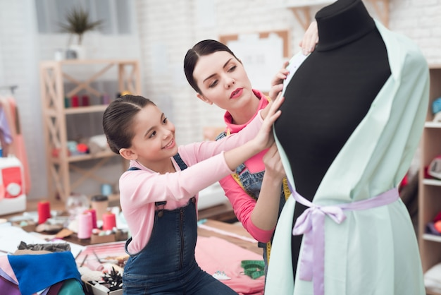 Pessoas experimentando roupas em um manequim.