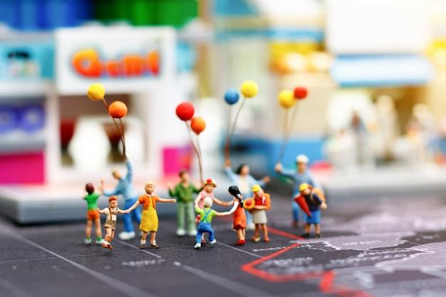 Pessoas, família e crianças em miniatura desfrutam com balões coloridos, conceito feliz dia da família.