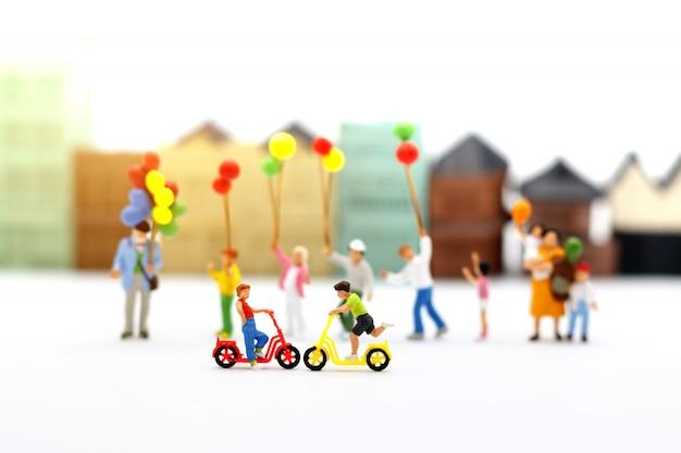 Pessoas, família e crianças em miniatura se divertem com balões coloridos.