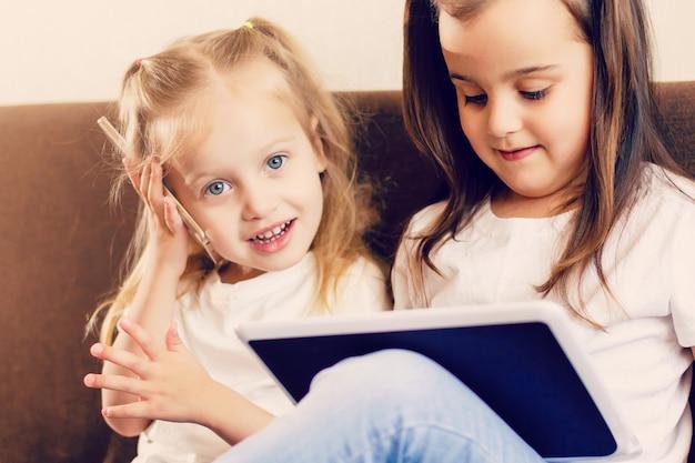 Pessoas, família, tecnologia e conceito das crianças - meninas felizes que jogam com o computador do pc da tabuleta em casa