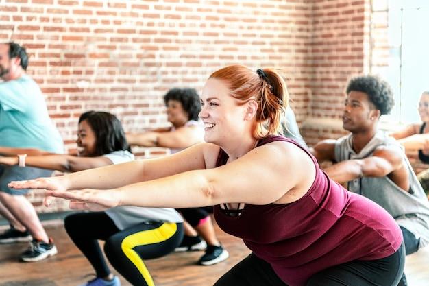 Pessoas fazendo agachamento na aula de fitness