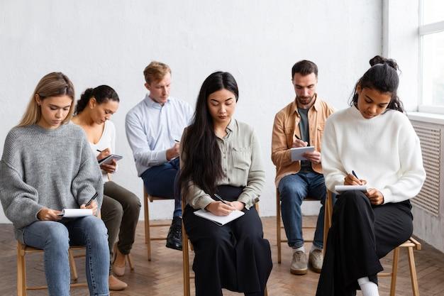 Pessoas fazendo anotações em uma sessão de terapia de grupo