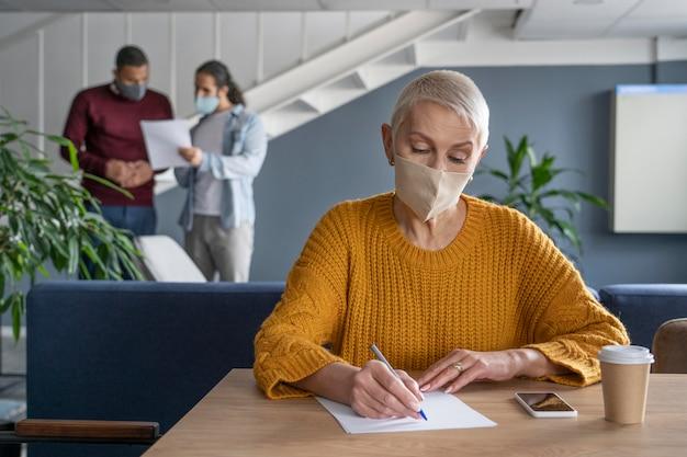 Pessoas fazendo coworking em restrições secretas Foto gratuita