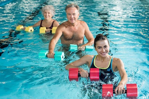 Pessoas fazendo exercícios com halteres aquáticos em uma piscina