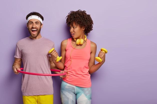 Pessoas fazendo exercícios, seguram halteres com as duas mãos