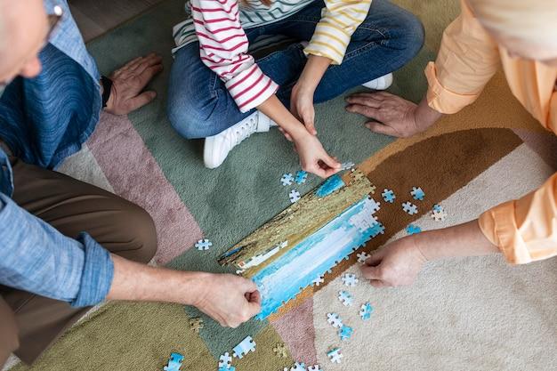 Pessoas fazendo quebra-cabeças no chão de perto
