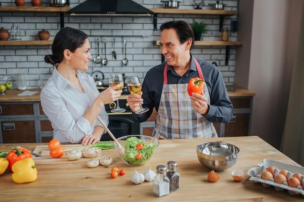 Pessoas felizes e positivas sentam juntos na cozinha à mesa