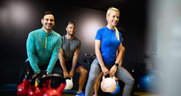 Pessoas felizes em forma de treino na aula de fitness no ginásio