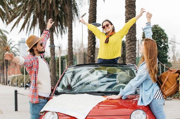 Pessoas felizes em pé perto de carro com roteiro