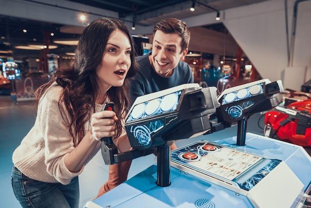 Pessoas felizes estão pilotando naves espaciais jogando no arcade.