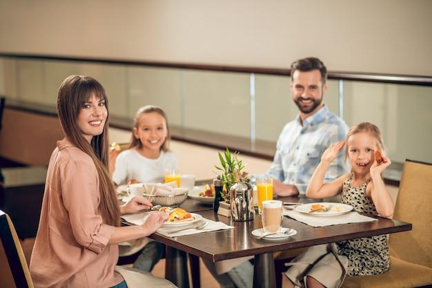 Pessoas felizes. família sorridente, sentada à mesa e parecendo feliz