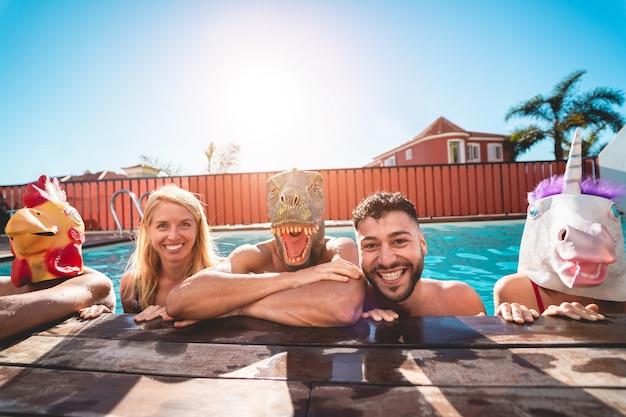 Pessoas felizes fazendo festa privada na piscina enquanto usava máscaras de animais engraçados