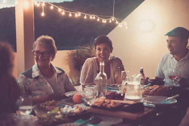 Pessoas felizes, idosos, adultos e jovens de estilo vintage juntos em um jantar com amigos em um restaurante ao ar livre com luzes de amizade