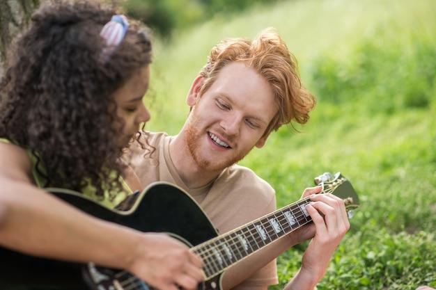 Pessoas felizes. jovem feliz e sorridente ruivo e garota com cabelo escuro encaracolado e guitarra preta, passando seu tempo de lazer na natureza