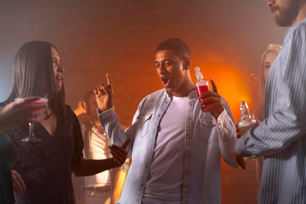 Pessoas felizes na festa com bebidas de perto