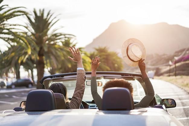 Pessoas felizes se divertindo no carro conversível nas férias de verão ao pôr do sol