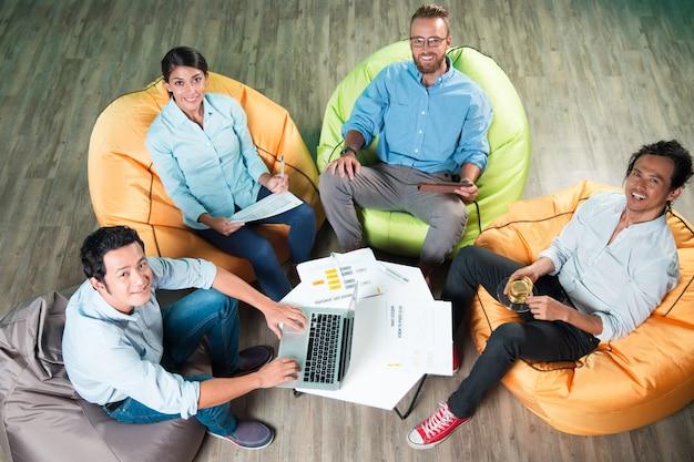 Pessoas felizes sentadas em cadeiras beanbag ao redor da mesa
