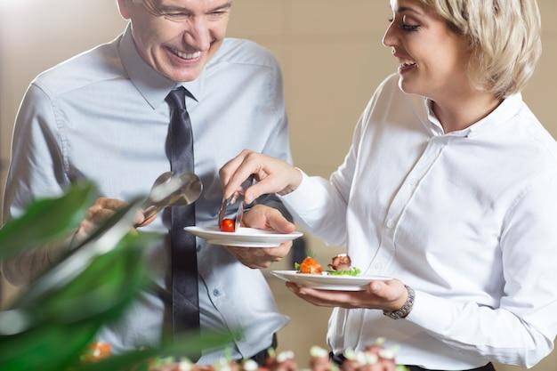 Pessoas felizes servindo-se com snacks
