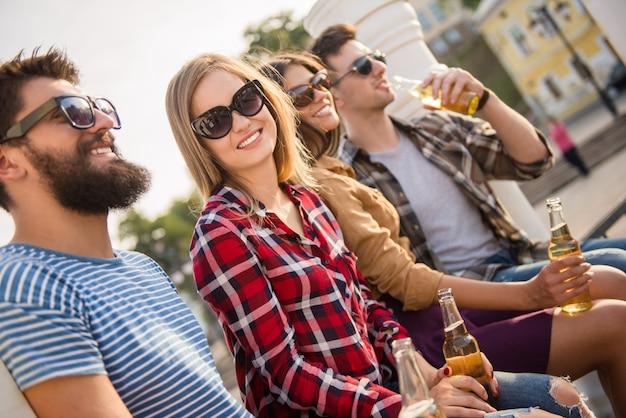 Pessoas felizes, sorrindo e bebendo.