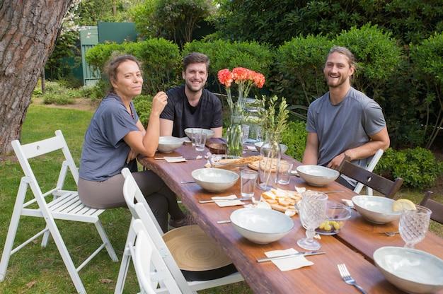 Pessoas felizes, tomando café da manhã na mesa de madeira no quintal