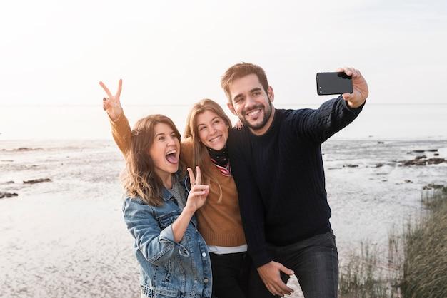 Pessoas felizes tomando selfie na beira-mar