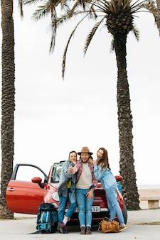Pessoas felizes tomando selfie perto de carro vermelho