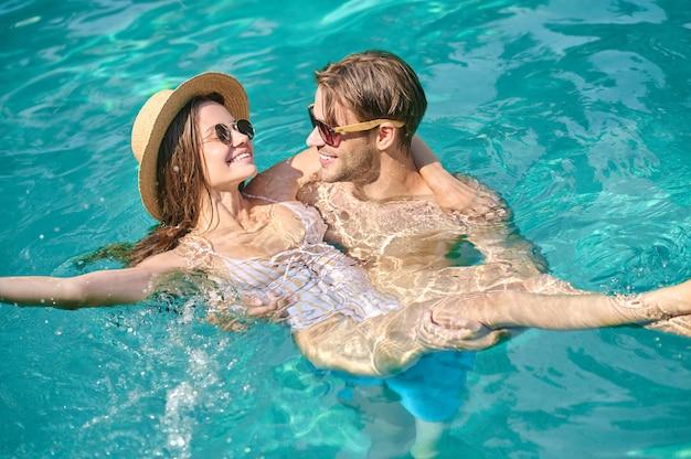 Pessoas felizes. um jovem casal feliz nadando em uma piscina