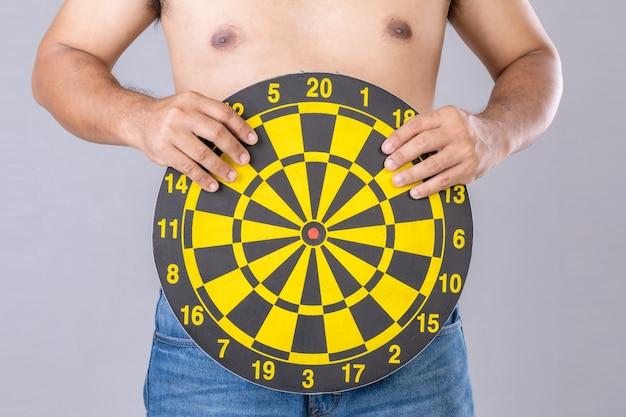 Pessoas gordas segurando um alvo de dardos amarelo redondo ao lado de sua barriga. alvo de perder o conceito de peso.