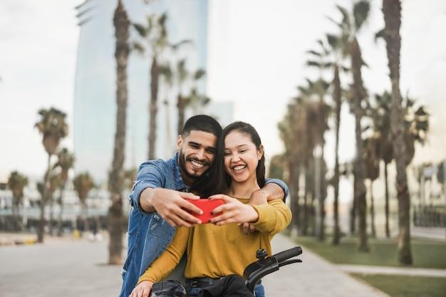 Pessoas hispânicas felizes se divertindo com uma bicicleta elétrica enquanto fazem selfie ao ar livre na cidade